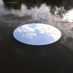 détail d'un flotteurs miroirs sur l'étang qui reflète le ciel
